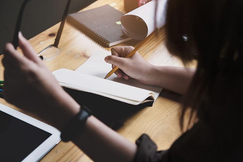 Frau, die in ein Notizbuch schreibt