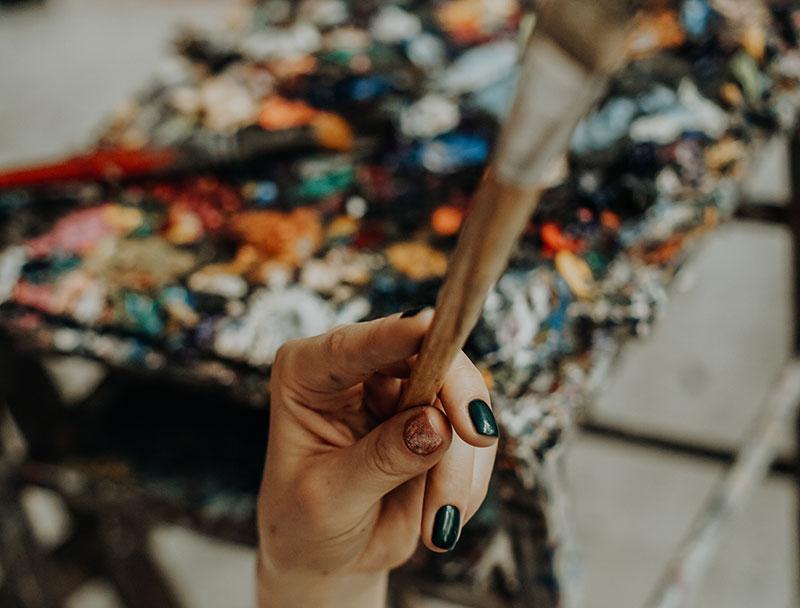 Foto von Künstlerin mit Pinsel in der Hand