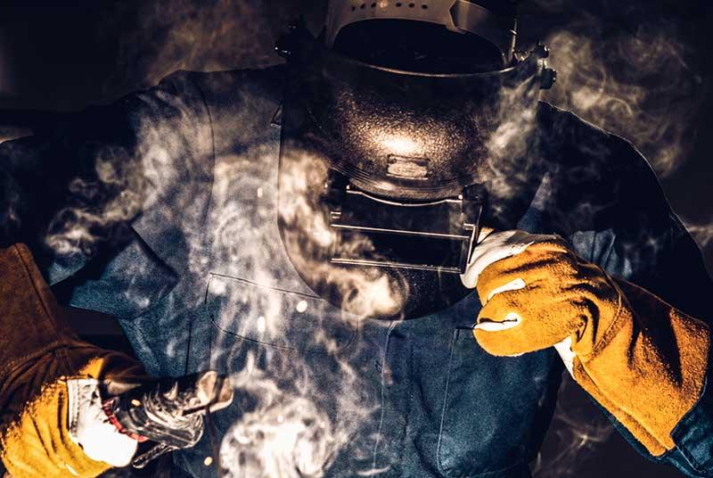 Foto mit Schweisser bei der Arbeit, Dampf steigt auf